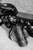 在摩托车附近的皮革背包 半在车库的黑摩托车 摩托车kaferacers 库存图片
