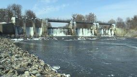 在摩拉瓦河、水力发电的动力火车,在冬天结冰的水中与冰和冰柱的测流堰下雪,在岸的石头 股票视频