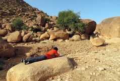 在摩洛哥的山的徒步旅行者休假,说谎在看他的智能手机的石头 库存图片