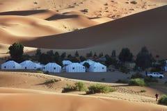 在撒哈拉大沙漠中沙丘的白色野营的帐篷,在帐篷人民附近是, Merzouga,摩洛哥 库存照片