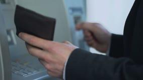 在撤出现金和收到帐户余额报告的ATM的男性插入的卡片 股票录像