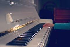 在播放曲调的钢琴的白色钥匙的手 妇女` s H 免版税库存图片