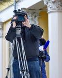 在操作和新闻工作者后的录影操作员采访 免版税库存图片