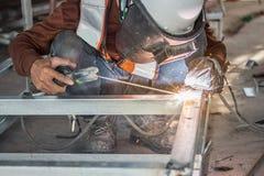在操作的焊工,雇员使用焊工机器的焊接U钢 免版税库存图片