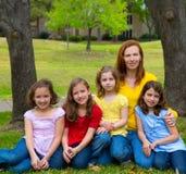 在操场公园照顾有女儿学生的老师 免版税库存照片
