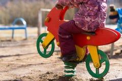 在操场的一个孩子坐玩具马 库存照片