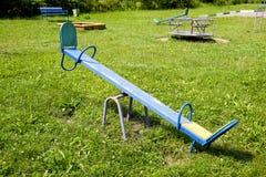在操场的儿童的摇椅 免版税库存图片