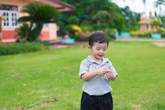在操场的小亚洲孩子在阳光下,浅D 免版税图库摄影