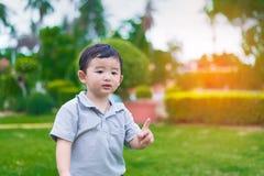 在操场的小亚洲孩子在阳光下,浅D 免版税库存照片