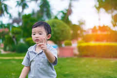 在操场的小亚洲孩子在阳光下,浅D 免版税库存图片