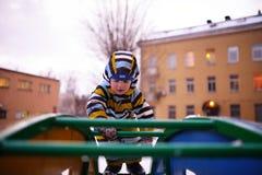 在操场的小儿童游戏在冬天 免版税库存照片