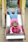 滑在操场的小山的小女孩 库存图片