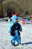 在操场的小男孩戏剧冬天 免版税库存图片