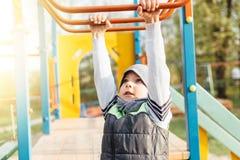 在操场的小男孩戏剧有迷离公园背景 免版税库存图片