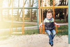 在操场的小男孩戏剧有迷离公园背景 免版税图库摄影