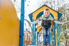 在操场的小男孩戏剧有迷离公园背景 免版税库存照片