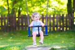在操场的愉快的笑的小孩女孩摇摆的乘驾 免版税图库摄影