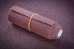 在擦亮的板料研磨材料的滚动的砂纸 免版税库存照片
