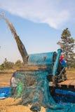 在收获期间,一个小组泰国农夫在东北泰国使用一个机器分离米仁,在米领域 库存图片