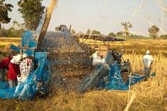 在收获期间,一个小组泰国农夫在东北泰国使用一个机器分离米仁,在米领域 免版税图库摄影