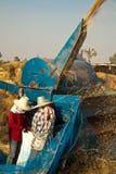 在收获期间,一个小组泰国农夫在东北泰国使用一个机器分离米仁,在米领域 库存照片