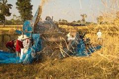 在收获期间,一个小组泰国农夫在东北泰国使用一个机器分离米仁,在米领域 免版税库存照片
