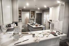 在改造的杂乱家庭厨房与橱门期间打开凌乱与油漆罐头、工具和肮脏的旧布 库存照片