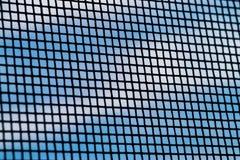 在放大下的蚊帐,以与白色云彩的蓝天为背景 库存照片