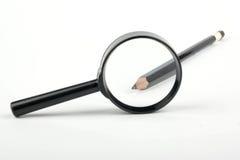 在放大镜的铅笔 免版税库存图片