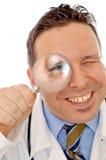 在放大镜的医生的眼睛 库存图片