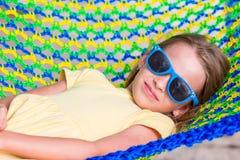 在放松在吊床的热带假期的可爱的小女孩 库存照片