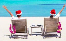 在放松在海滩的圣诞老人帽子的年轻夫妇 免版税库存照片
