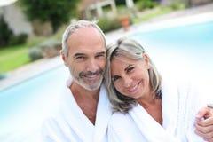 在放松在温泉旅馆里的浴巾的夫妇 免版税库存照片