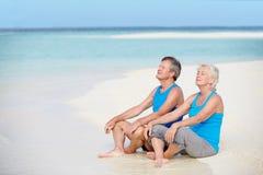 在放松在美丽的海滩的体育衣物的资深夫妇 库存图片