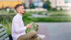 在放松在长凳听的音乐的耳机的可爱的行家男性开会使用智能手机 股票录像