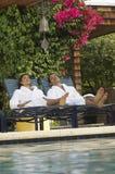 在放松由游泳池的浴巾的夫妇 免版税库存照片