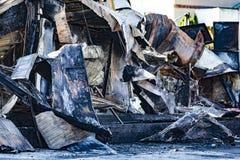 在放火火以后的损坏的产业超级市场与扭转的金属木结构烧伤残骸在强烈的灼烧的火以后的 免版税库存照片