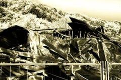 在放火火以后的损坏的产业超级市场与扭转的金属木结构烧伤残骸在强烈的灼烧的火以后的 免版税库存图片