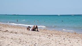 在放置在沙子的游泳衣的美国黑人的鬃毛在oceal附近 免版税库存图片