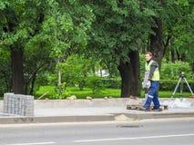 在放置新的瓦片工作在城市街道 在地板放置新的瓦片 铺在城市 一个人运载大厦瓦片 ru 免版税库存照片