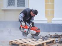 在放置新的瓦片工作在城市街道 在地板放置新的瓦片 铺在城市 锯瓦片的工作者 俄国 免版税库存图片