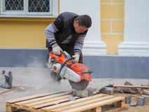 在放置新的瓦片工作在城市街道 在地板放置新的瓦片 铺在城市 锯瓦片的工作者 俄国 免版税图库摄影