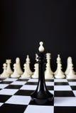 在敌对队前面的单独棋国王 不同等的争斗 免版税库存图片
