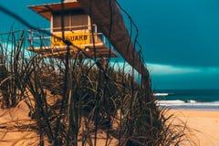 在救生员客舱附近的篱芭在海滩 库存图片