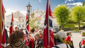 在教会前面的挪威人在国旗之间 免版税库存图片