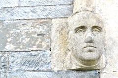 在教会墙壁上的石顶头细节 免版税库存照片