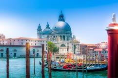 在教会大教堂二圣玛丽亚della致敬和运河的威尼斯视图有长平底船的 库存图片