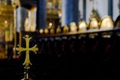 在教会里面的金属金黄被环绕的十字架 免版税库存照片