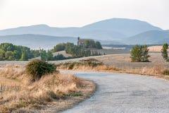 在教会附近的乡下公路在Navarra,西班牙 免版税库存照片