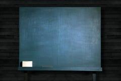 在教室倒空在木墙壁上的绿色黑板 免版税库存图片